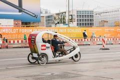 柏林, 2017年10月1日:未知的年长自行车出租汽车司机搭载路的乘客通过人和广告横幅 库存照片