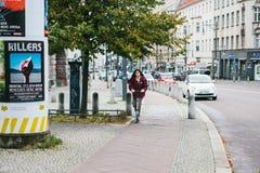 柏林, 2017年12月12日:滑行车的一个女孩在大厦旁边乘坐沿城市街道的一条特别自行车道路 库存图片
