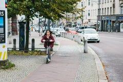 柏林, 2017年12月12日:滑行车的一个女孩在大厦旁边乘坐沿城市街道的一条特别自行车道路 库存照片