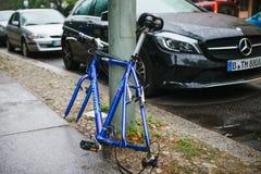 柏林, 2017年10月2日:蓝色自行车附有与锁的街道柱子站立,不用轮子在被窃取以后  库存照片