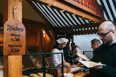 柏林, 2017年10月03日:面包师在街道面包店工作在慕尼黑啤酒节A满意的买家叶子用薄饼 库存照片
