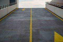 柏油路、与难看的东西表面纹理的车道对多层的停车场,车库和交通的对比的黄色颜色 免版税库存照片