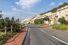 柏油路和海滩前的大厦和蓝色多云地平线 库存图片