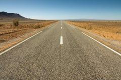 柏油路在一片岩石沙漠 库存照片
