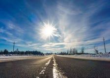 柏油路在多雪的冬天在美好的冷淡的晴天 旅途,旅行, trave 免版税库存图片