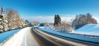 柏油路在多雪的冬天在美好的晴天 免版税库存照片