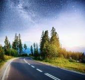 柏油路在繁星之夜天空和银河下 图库摄影
