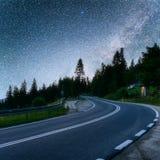 柏油路在繁星之夜天空和银河下 库存图片
