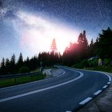 柏油路在繁星之夜天空和银河下 免版税库存图片