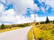 柏油路导致电视发射机的和监视在Praded山, Hruby Jesenik,捷克山顶耸立  免版税图库摄影