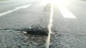 柏油路的坑洼在城市 免版税库存照片