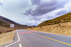 柏油路高方式空的弯曲的路覆盖,天空和山 免版税库存照片