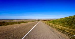 柏油路,有宽领域的一条高速公路的美好的全景 免版税库存图片