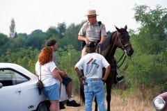 某些人与马的一位警察谈话 免版税库存照片