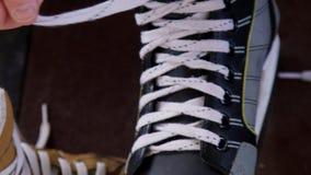 某人供以人员黑手的鞋带和曲棍球的灰色冰鞋 影视素材