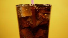 某人混合与吸管的可乐鸡尾酒 杯泡沫腾涌的饮料冰块 影视素材