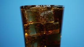 某人混合与吸管的可乐鸡尾酒 玻璃有很多焦炭泡沫腾涌的饮料 股票录像