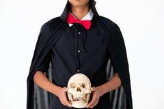 某人黑礼服看起来的巫婆在白色ba的藏品头骨 免版税图库摄影
