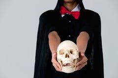 某人黑礼服看起来的巫婆在白色ba的藏品头骨 免版税库存照片