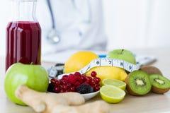 某果子例如苹果、猕猴桃、柠檬和莓果在营养师桌上 免版税库存图片