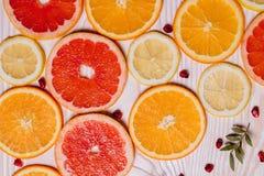 柑桔切成了两半-桔子,柠檬,蜜桔,在木背景的葡萄柚 库存照片