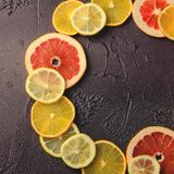 柑桔切片柠檬,桔子,在圈子形状的葡萄柚在黑暗的背景 库存照片