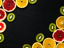 柑橘和猕猴桃构筑在黑色被构造化的背景的模板 与桔子、葡萄柚和猕猴桃切片的照片在角落 果子fla 库存照片
