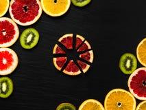 柑橘和猕猴桃构筑在黑色被构造化的背景的模板 与桔子、葡萄柚和猕猴桃切片的照片在角落 果子fla 图库摄影