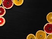 柑橘在黑色被构造化的背景的框架模板 与桔子和葡萄柚切片的照片在角落 果子flatlay与地方 免版税库存图片