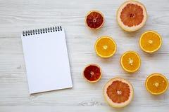 柑橘水果桔子,葡萄柚,与空白的笔记薄的西西里人的桔子在白色木背景,从上面 平的位置 免版税库存照片