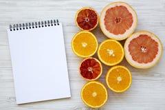 柑橘水果桔子,葡萄柚,与空白的笔记薄的西西里人的桔子在白色木背景,从上面 平的位置 库存照片