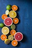 柑橘水果的分类在蓝色背景,顶视图的 桔子,葡萄柚,蜜桔,石灰,柠檬-有机果子, vegetari 库存照片