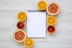 柑橘水果西西里人的桔子,葡萄柚,橙色与在白色木背景的笔记本,从上面 平的位置 库存照片