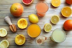 柑橘汁三块玻璃用橙色果子柠檬和葡萄柚 免版税库存照片