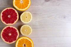柑橘水果切了背景桔子,柠檬,在明亮的木背景的葡萄柚 免版税图库摄影