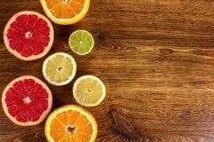 柑橘水果切了背景桔子,柠檬,石灰,在木背景的葡萄柚 库存照片