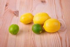 柑橘水果柠檬石灰桔子 三个黄色柠檬和两鲜绿色的石灰 柠檬和石灰在一张轻的木桌上 热带果子 免版税库存图片