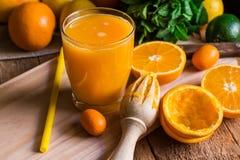 柑橘水果桔子柠檬撒石灰cumquat,新鲜薄荷,绞刀,在玻璃的新近地果汁 免版税库存图片