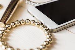 染睫毛油、手机和金镯子 免版税库存图片