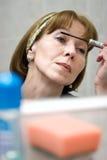 染睫毛油成熟放置的妇女 库存图片