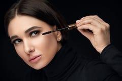 染睫毛油构成 把黑染睫毛油放的秀丽模型在睫毛上 免版税库存照片