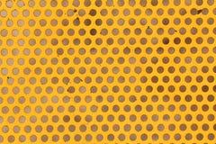染黄被绘的圈子被穿孔的金属盘区纹理和背景 免版税图库摄影