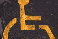 染黄黑沥青表面上的被绘的轮椅标志 图库摄影