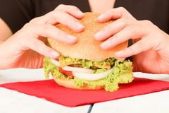 染黑加工好的妇女准备吃汉堡包 库存照片
