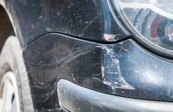 染黑在崩溃事故的损坏的汽车与被抓的油漆和消弱的后档金属身体,选择聚焦的关闭 免版税库存照片