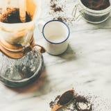 染黑在烧瓶和白色杯子,方形的庄稼的被过滤的咖啡 库存图片