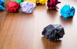 染黑在黑褐色木桌上的被弄皱的纸球与小组  库存图片