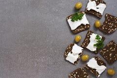 染黑敬酒的灰色表面上的面包用乳酪和五谷 在视图之上 库存图片