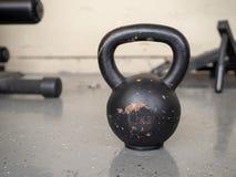 染黑, 10 kg kettlebell坐与空间的坚硬健身房地板 免版税图库摄影
