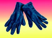 染黑与在桃红色和黄色背景隔绝的蓝色皮手套 库存图片